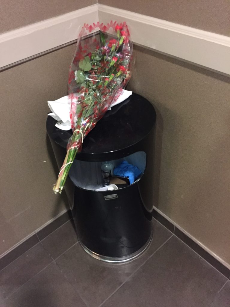 Wrapped bouquet of flowers on top of a trash can