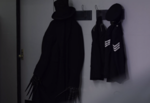 The Babadook's hat and cloak next to a police officer's